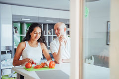 Woman cuts vegetables together in the kitchen Stock Photography