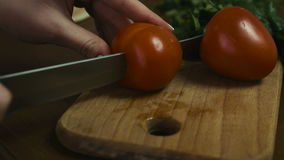 Woman cuts a whole tomato to two big slices on a wooden plate, close-up  footage. Woman cuts a whole tomato to two big slices on a wooden plate,  close-up stock video footage