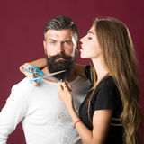 Woman cuttin male beard Stock Images