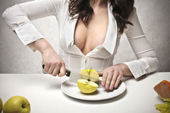 Woman cutting an apple. In a half with a big knife Royalty Free Stock Photos