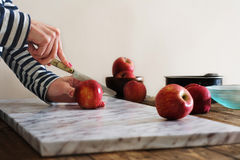 Woman cutting apples on the table Royalty Free Stock Photos