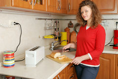 Woman cutting bread. At kitchen Stock Photos