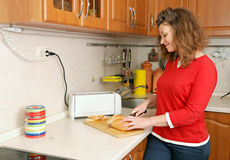 Woman cutting bread. At kitchen Royalty Free Stock Images