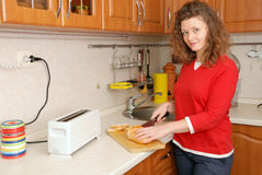 Woman cutting bread. At kitchen Stock Images