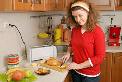 Woman cutting bread. At kitchen Royalty Free Stock Image