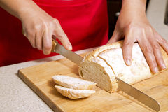 Woman cutting bread Stock Photo