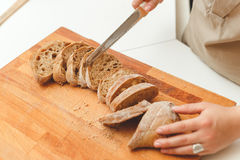 Woman cutting a bread ciabatta with knife in kitchen Stock Photography