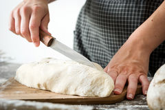 Woman cutting bread dough on wood. En table Stock Photography