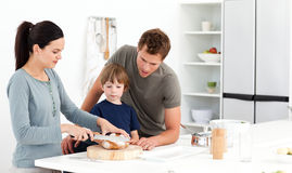 Woman cutting bread for her family. Lovely woman cutting bread for her son ad husband in the kitchen Royalty Free Stock Photos