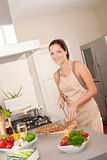 Woman cutting bread in the kitchen. Smiling woman cutting bread in the kitchen Stock Photography