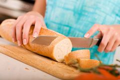 Woman cutting bread on the kitchen Stock Photography
