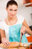 Woman cutting bread on the kitchen. Young woman cutting bread on the kitchen Stock Image