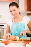 Woman cutting bread on the kitchen Stock Photos