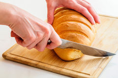 Woman cutting bread by knife. On wooden board Stock Photos