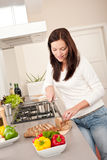 Woman cutting bread in modern kitchen. Young woman cutting bread in modern kitchen Royalty Free Stock Image
