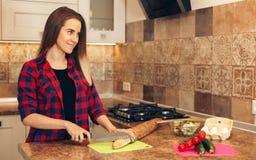 Woman cutting bread, preparing breakfast in kitchen. Young woman cutting bread for breakfast Royalty Free Stock Image
