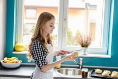 Woman cutting a bread roll with knife in kitchen. Caucasian blond woman cutting a bread roll with knife in kitchen. Standing in front of a window in the kitchen Stock Image