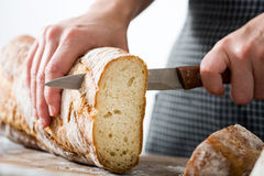 Woman cutting bread on a rustic wood. En table Stock Photography