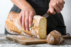 Woman cutting bread on a rustic wood. En table Royalty Free Stock Photo