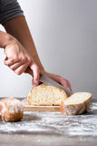 Woman cutting bread on a rustic wood. En table Stock Photo