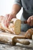 Woman cutting bread on wood. En table Stock Image