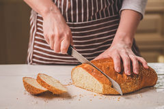 Woman cutting bread on wooden board. Bakehouse. Bread production. A woman in a striped apron Royalty Free Stock Photography