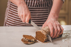 Woman cutting bread on wooden board. Bakehouse. Bread production. A woman in a striped apron Royalty Free Stock Image