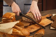 Woman cutting bread on wooden board. Unrecognizable female chef preparing healthy sandwiches, side view, copy space Royalty Free Stock Images