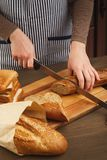 Woman cutting bread on wooden board. Unrecognizable female chef preparing healthy sandwiches, side view, copy space Stock Photo
