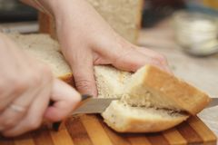 Woman cutting a bread on the wooden desk. A Woman cutting a bread on the wooden desk Royalty Free Stock Image
