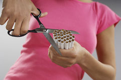 Woman Cutting Bundle Of Cigarettes. Midsection of an African American woman cutting bundle of cigarettes Stock Image