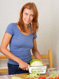 Woman cutting cabbage Stock Images