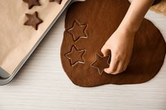 Woman cutting cookies from raw dough. On table Royalty Free Stock Images