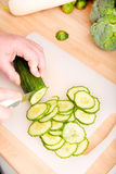 Woman cutting cucumber Royalty Free Stock Images