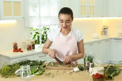 Free Woman Cutting Cucumber In Kitchen. Preparing Pickles Stock Image - 193434041