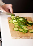 Woman in cutting cucumber on kitchen board. Royalty Free Stock Image