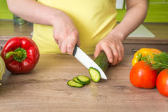 Woman cutting cucumber for salad - fresh vegetables concept Stock Photos