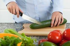 Woman cutting cucumber Stock Image