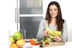 Woman cutting cucumber and vegetables Stock Images