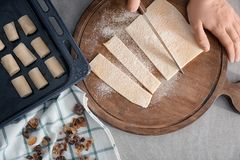 Woman cutting flaky dough on wooden board,. Top view Stock Photo