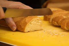 Woman cutting french loaf Royalty Free Stock Images
