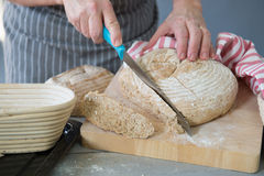 Woman cutting fresh baked bread Stock Photos