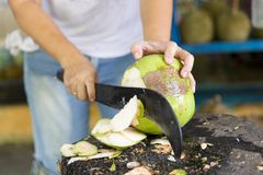 Woman cutting fresh coconut at the market Royalty Free Stock Image