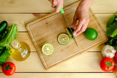 Woman cutting fresh green lime on wooden board Royalty Free Stock Photos