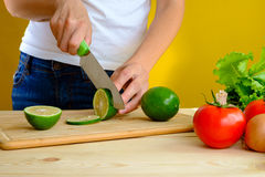 Woman cutting fresh green lime on wooden table Stock Image