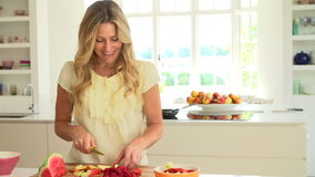 Woman Cutting Fresh Summer Fruit In Kitchen stock footage