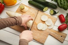 Woman cutting fresh turnip on wooden board. Natural eating, preparing healthy dietic vegetable salad at kitchen, top view Stock Photos