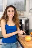 Woman cutting fruit in the kitchen Royalty Free Stock Images