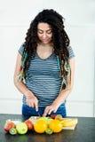 Woman cutting fruits on chopping board Stock Photo