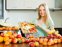 Woman cutting fruits for sala Stock Images